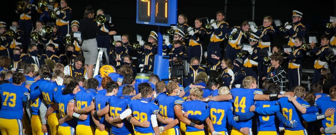 Football team listening to band play the alma mater
