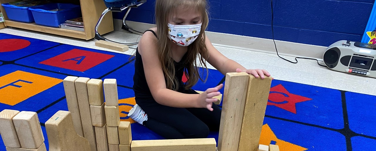 a future engineer is building a structure with blocks