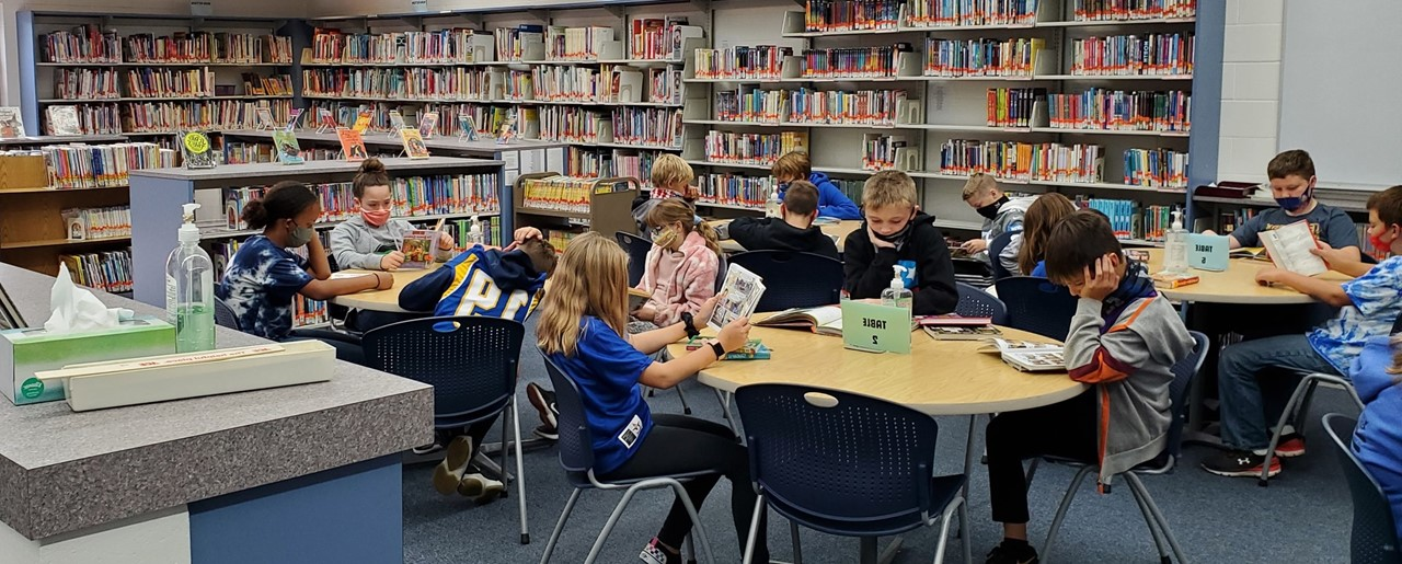 5th graders reading books in library