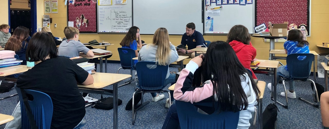 Mr. Ruane reads to 8th grade students